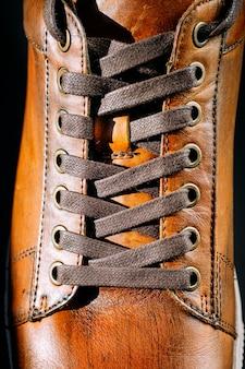 Gros plan d'une chaussure en cuir marron pour hommes. laçage sur chaussures