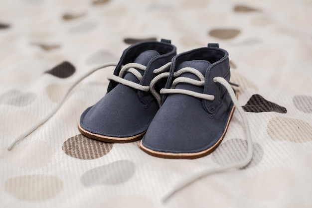 Gros Plan De Chaussures Bébé Garçon Sur Un Lit Photo gratuit