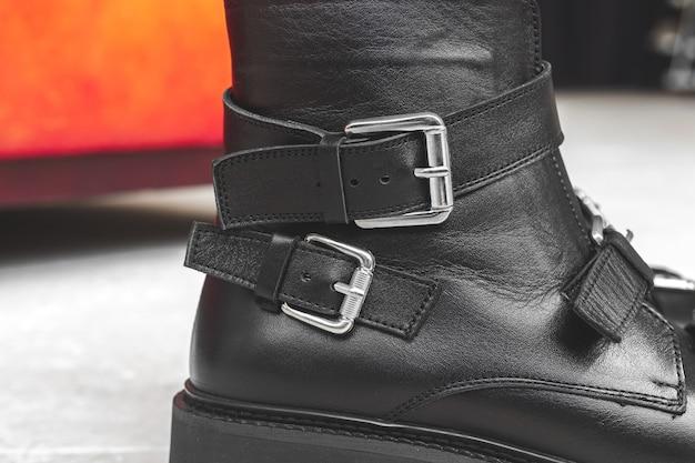 Gros plan sur les chaussures en cuir noir et détails textiles, photo de concept de conception de bottes