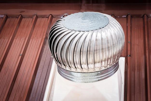 Gros plan sur une cheminée de ventilation sur le toit qui dépend du vent pour tourner.