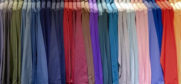 Gros plan de chemises multicolores sur des cintres, fond de tissu de vêtements colorés