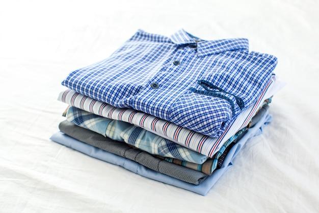 Gros plan de chemises repassées et pliées sur la table à la maison