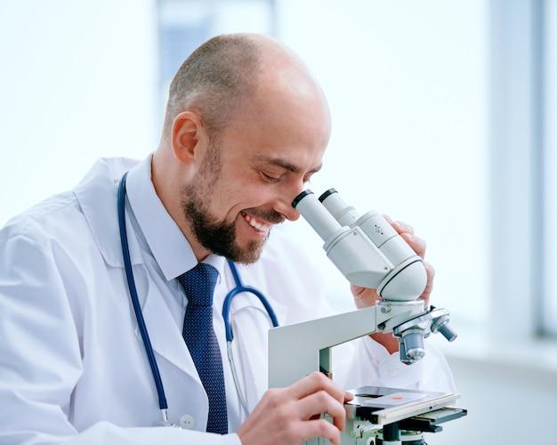 Gros plan sur le chercheur à la recherche à travers un microscope dans un laboratoire médical