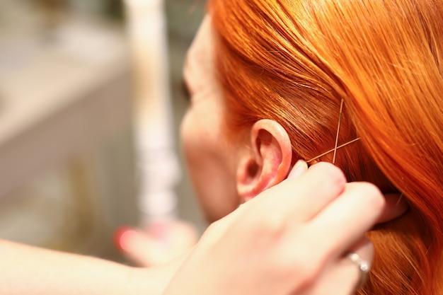 Gros plan des cheveux roux de luxe féminin avec des accessoires dorés