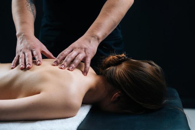 Gros plan d'un chiropraticien massant une jeune femme allongée sur une table de massage, poussant sur la colonne vertébrale. le masseur place les vertèbres dans la colonne vertébrale thoracique sur fond noir. concept de soins spa de massage.