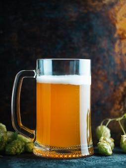 Gros plan d'une chope de bière de blé non filtrée et de houblon vert