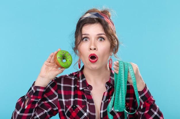Gros plan choqué surpris jeune belle femme regardant un ruban à mesurer et tenant un beignet vert dans les mains posant
