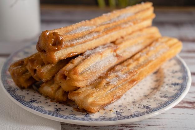 Gros plan de churros hispaniques typiques remplis de dulce de leche dans une assiette vintage sur de vieilles planches.