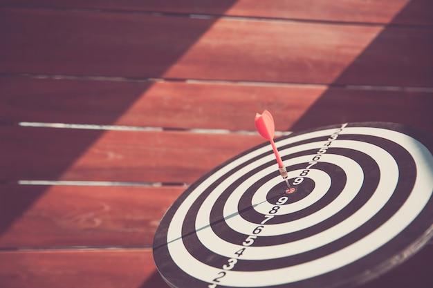Gros plan, la cible a une flèche de fléchette frappant le centre.