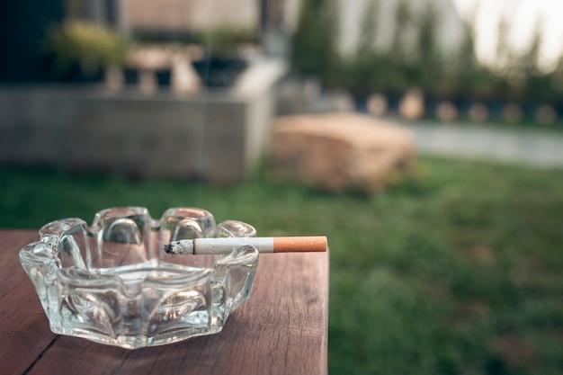 Gros plan de la cigarette sur le bord du cendrier sur la table en bois.