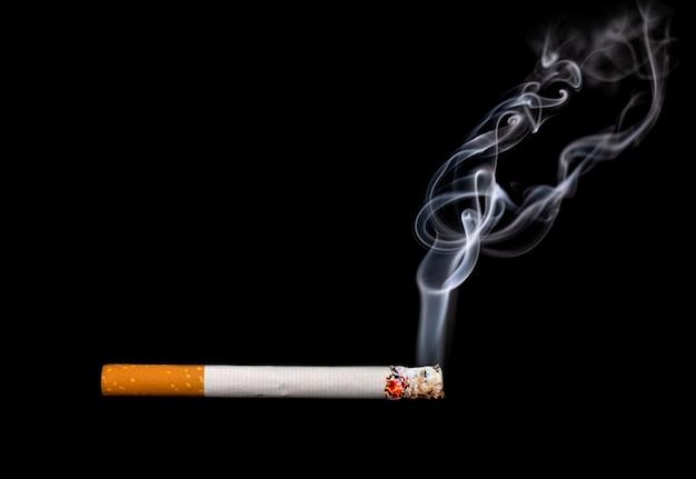 Gros plan d'une cigarette avec de la fumée montrant sur fond noir