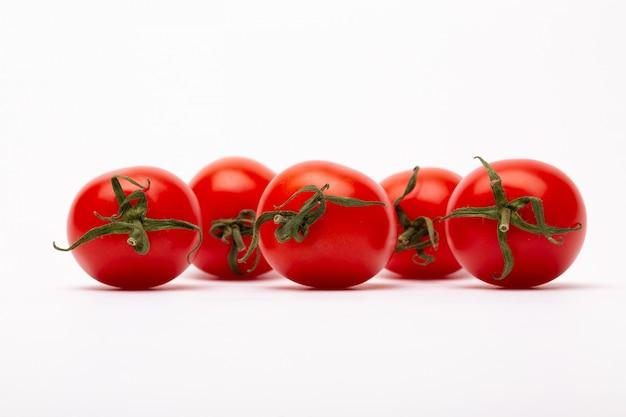 Gros plan de cinq tomates cerises sur un mur blanc - parfait pour un blog culinaire