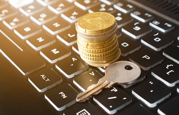 Gros plan de la clé et de la pile de pièces sur le clavier noir. concept d'assurance