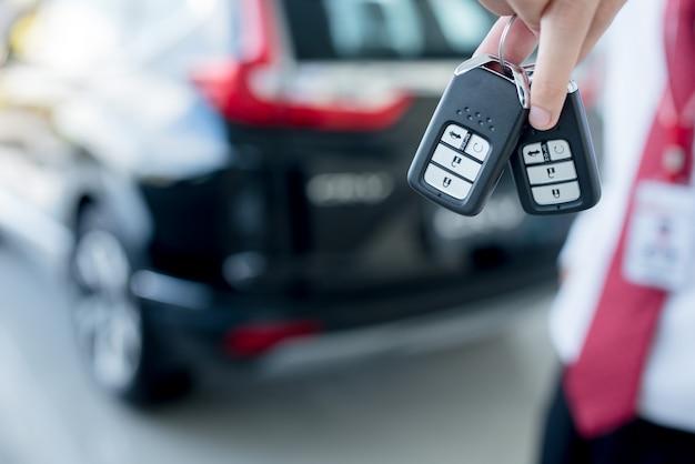 Gros plan d'une clé de voiture - un jeune homme tenant une nouvelle clé de voiture dans la salle d'exposition de voiture, nouvelle clé