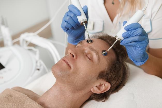 Gros plan d'un client masculin obtenant un traitement de soin du visage par électrolyse au salon de beauté