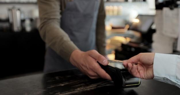 Gros plan client payer à l'aide d'une carte de crédit dépenser de l'argent au café