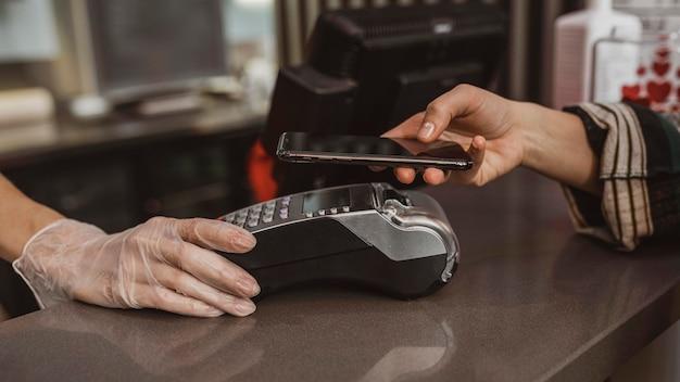 Gros plan d'un client qui paie sa facture de café