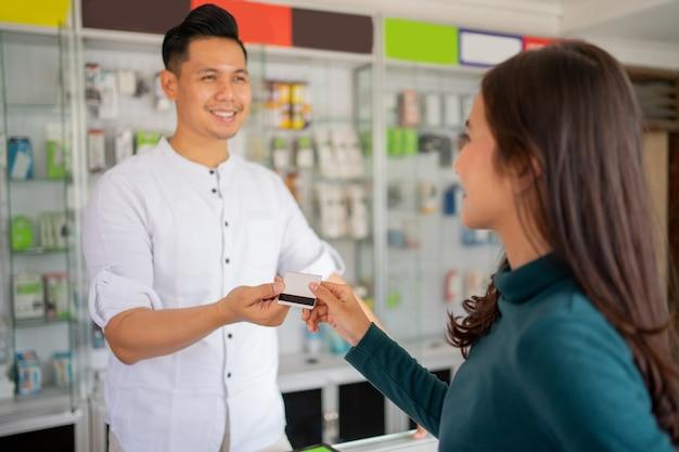Gros plan d'une cliente donnant une carte de crédit à un homme pour un paiement sans numéraire