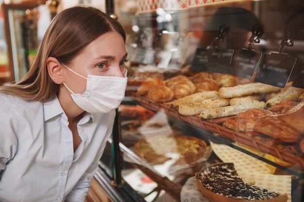 Gros plan d'une cliente portant un masque médical au magasin de boulangerie, en choisissant le dessert à acheter