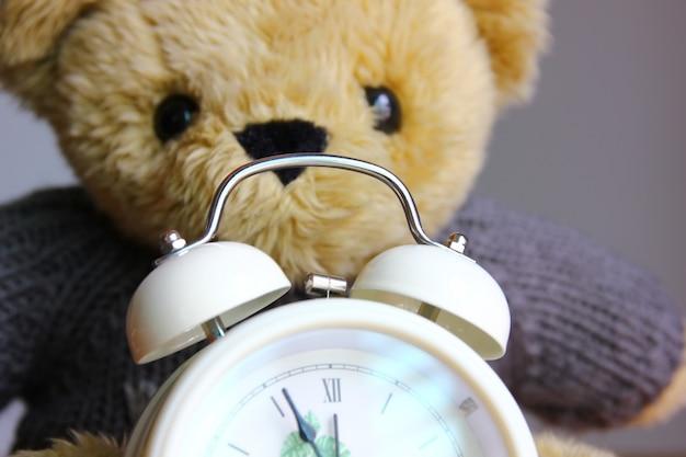 Gros plan sur la cloche du réveil avec fond d'ours en peluche