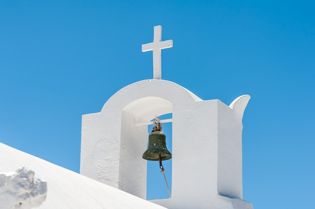Gros plan d'un clocher blanc avec croix à santorin
