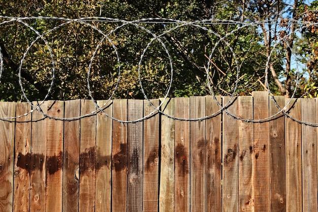 Gros plan d'une clôture en bois avec du fil de fer barbelé