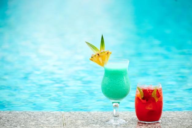 Gros plan sur des cocktails de fruits rafraîchissants d'été colorés placés au bord de la piscine
