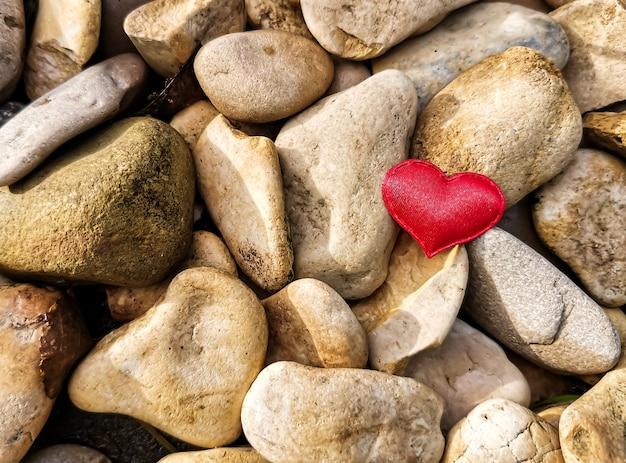Gros plan d'un coeur rouge sur des pierres rondes dans les rayons du soleil.
