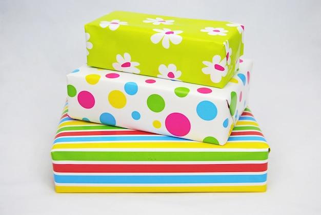 Gros plan de coffrets cadeaux colorés emballés sur une surface blanche