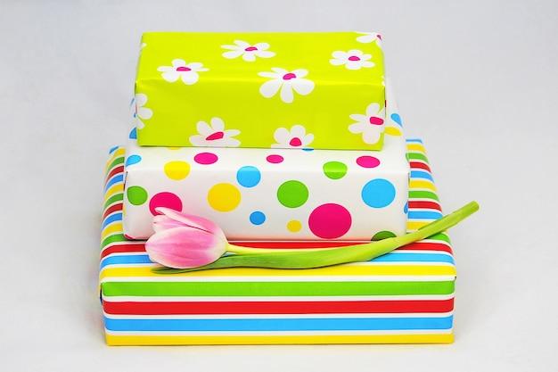 Gros plan de coffrets cadeaux colorés emballés et une tulipe sur une surface blanche
