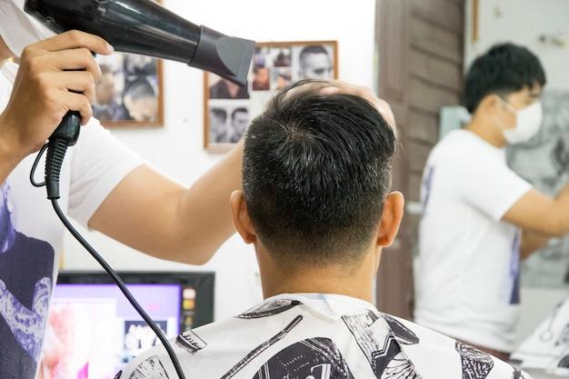 Gros plan d'un coiffeur homme avec sèche-cheveux au salon de coiffure.