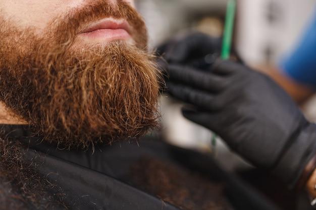 Gros plan d'un coiffeur professionnel masculin servant le client avec une grosse barbe épaisse par une tondeuse