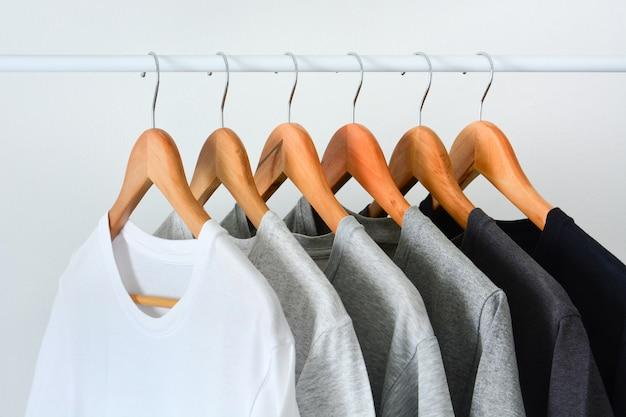 Gros plan d'une collection de couleurs noire, grise et blanche (monochrome) suspendue à un cintre en bois dans un placard ou un porte-vêtements