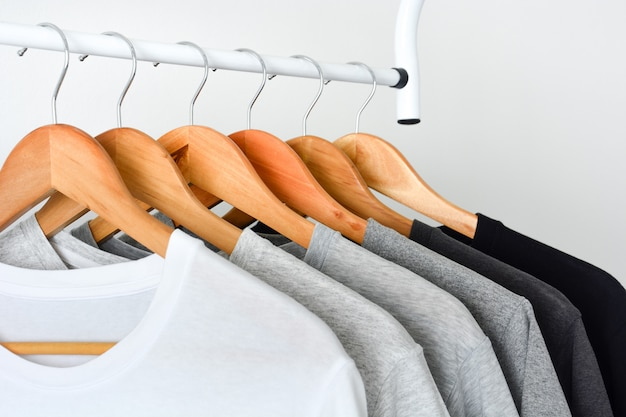 Gros plan d'une collection de t-shirts noirs, gris et blancs suspendus sur un cintre en bois