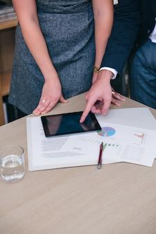 Gros plan sur des collègues méconnaissables utilisant une tablette électronique et des documents lors d'une réunion d'affaires