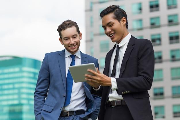 Gros plan de collègues souriants utilisant la tablette à l'extérieur