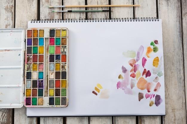 Gros plan, de, coloré, palette, pinceaux, et, papier, sur, surface bois