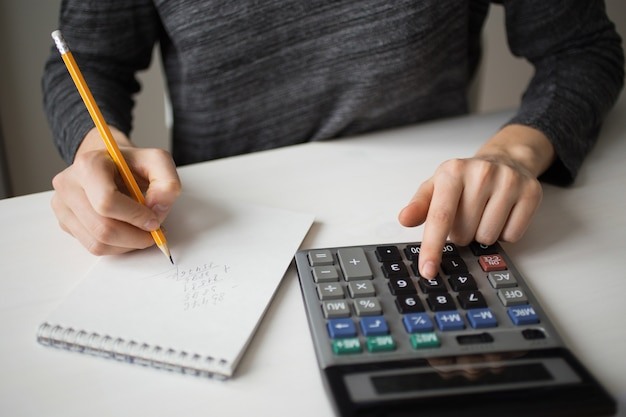 Gros plan de comptable utilisant la calculatrice et l'écriture