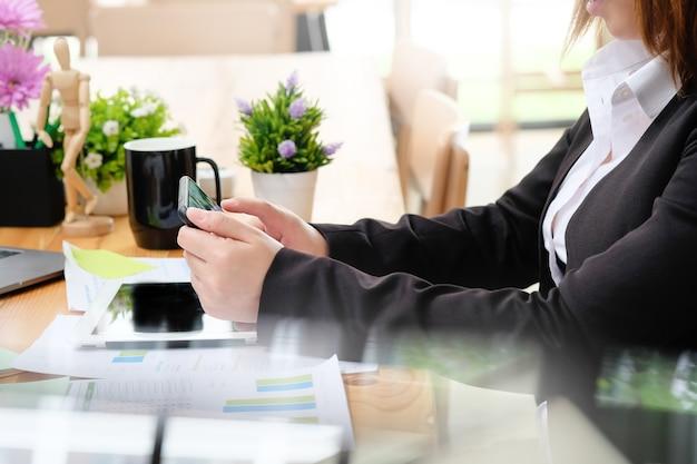 Gros plan de conférence de femme d'affaires sur smartphone en milieu de travail.