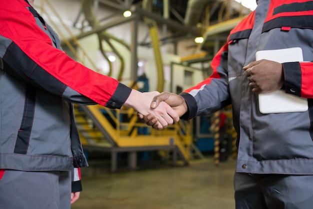 Gros plan de contremaîtres multiethniques méconnaissables en uniforme de poignée de main en magasin d'usine