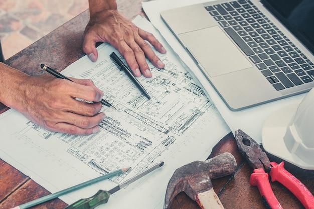 Gros plan sur le contrôle de la main sur le projet de construction de construction immobilière de conception de plan de papier