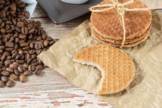 Gros plan des cookies stroopwafel avec une bouchée à côté des grains de café.