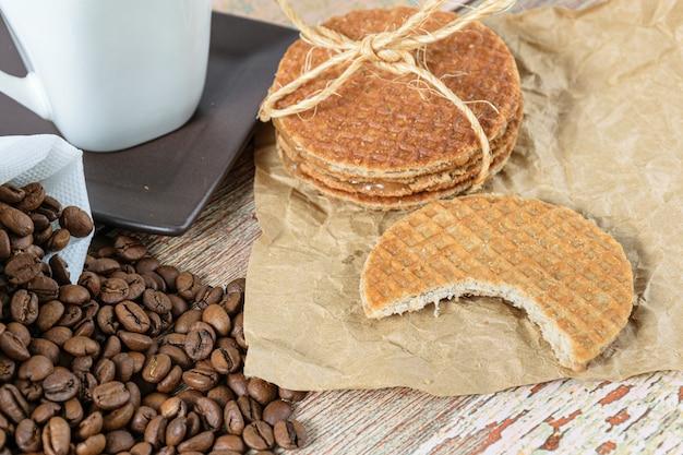Gros plan des cookies stroopwafel avec une bouchée à côté des haricots et une tasse de café.