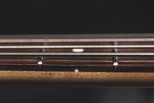 Gros plan des cordes sur le manche d'une guitare basse sur un fond sombre flou.