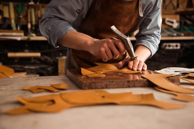 Gros plan d'un cordonnier homme travaillant avec du cuir