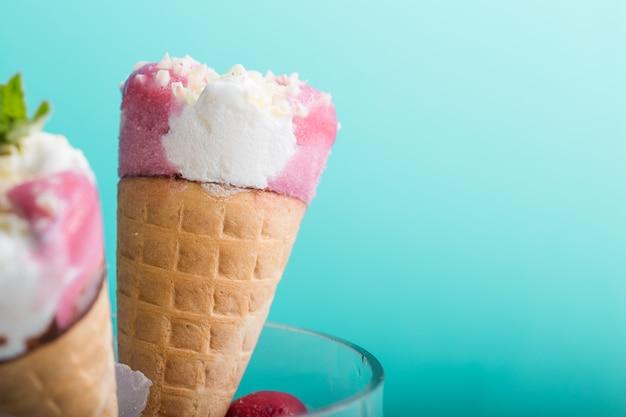 Gros plan de cornet de crème glacée. cuillère à glace rose en cône de gaufre sur fond bleu. saveur fraise ou framboise dessert sucré décoré de paillettes colorées, gros plan