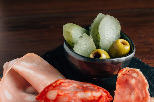 Gros plan de cornichons et d'olive dans une tasse noire avec des coupes à froid sur plaque de pierre noire.
