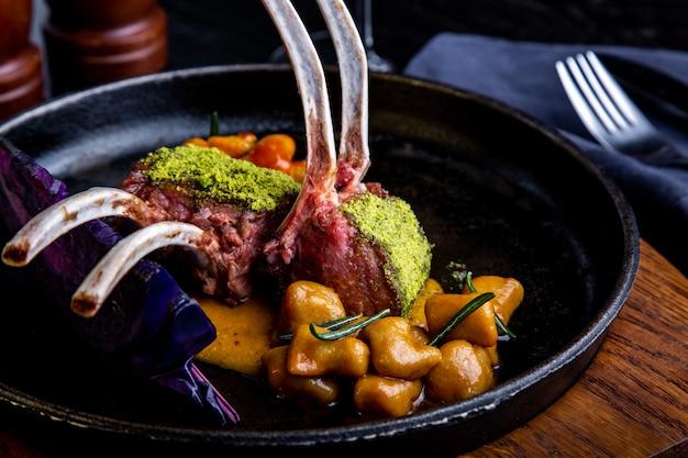 Gros plan de côtelettes d'agneau aux légumes avec une sauce au caramel, au poivre et aux épices dans un restaurant.