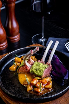 Gros plan de côtelettes d'agneau avec des légumes avec une sauce au caramel, poivre et épices dans un restaurant.