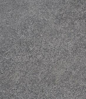Gros plan sur la couleur grise et le vieux sol en ciment à texture rugueuse.